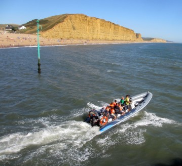A speed boat takes to the water in Lyme Bay with the cliffs on the Jurassic Coast as a back drop. https://idrismartin.wordpress.com/