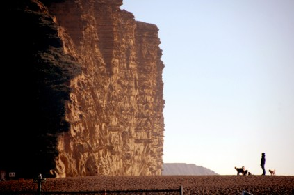 West Bay Dorset on the Jurassic Coast Mid Morning. + 5 degrees C in the sun on the Jurassic Coast. Despite the temperature a few hardy souls enjoy a walk on the pebble beachwith their dogs below the iconic cliffs.