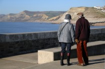 West Bay Dorset on the Jurassic Coast Mid Morning. + 5 degrees C in the sun on the Jurassic Coast. A couple enjoy the view from the harbour breakwater. https://idrismartin.wordpress.com/