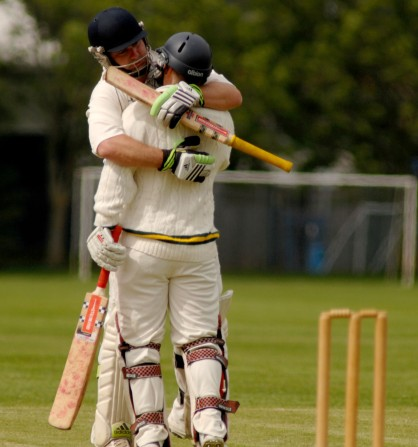 Keiron Womble is congratulated by his team mate after scoring his century.