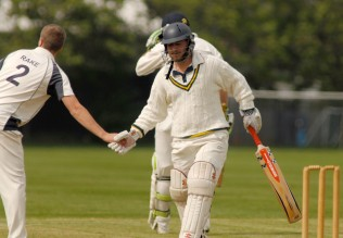 Keiron Womble is congratulated by a Parley player after scoring his century.