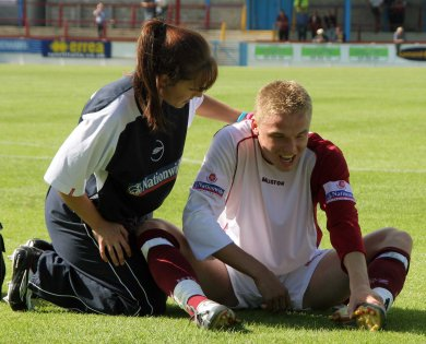 Carshalton full back Stuart Booth cops one in the crown jewels & gets some tender loving care from phyiso Shelly Sprigings.