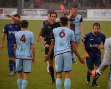 As the rain lashes the Bob Lucas Stadium Terras defender Calvin Brooks pleads his innocence but still sees red from referee Alex Blake for a second bookable offence. https://idrismartin.wordpress.com/